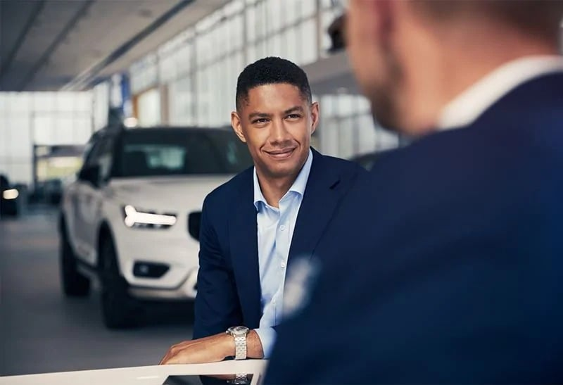 A man sitting with a Volvo representative